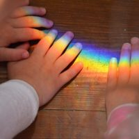 Photo of children's hands with rainbow light shining on them.